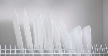 Row of clean white plates in the closet