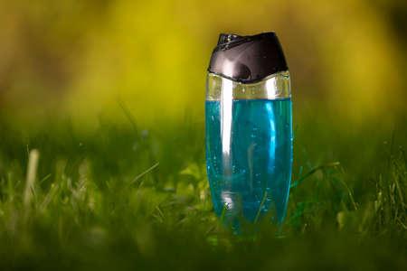 Mockup of blue shampoo bottle in a grass