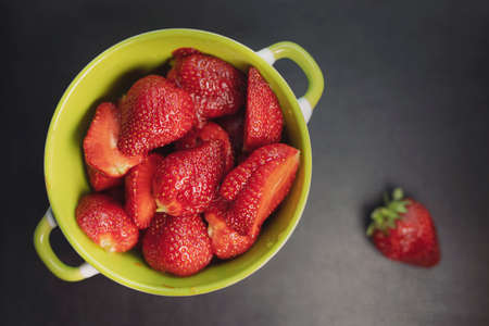 Plate with strawberries, black background