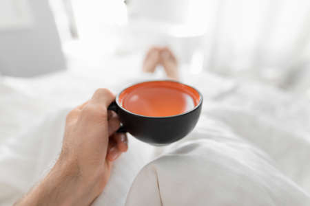 1st person view, man drinking morning tea in a bed