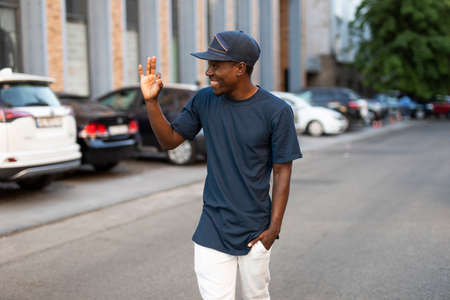 Happy african american man greets a friend waving his hand walking in city street, he glad to see you Foto de archivo