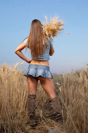 Sexy mujer campesina en minifalda con espiguillas de trigo en un campo