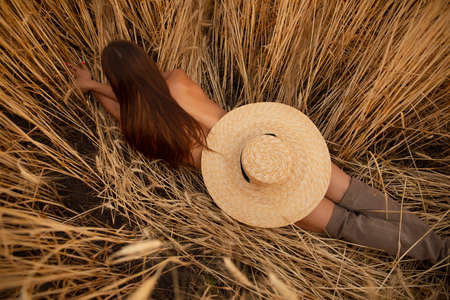 Naked woman lying on a field with hat, nudes at nature Standard-Bild