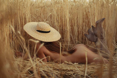 Naked woman lying on a field with hat, nudes at nature 스톡 콘텐츠