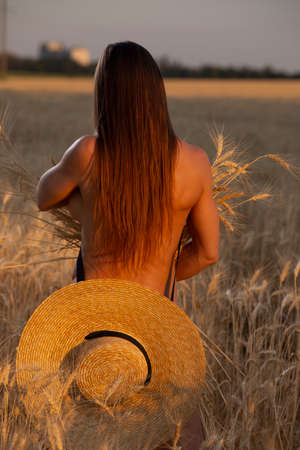 Back of naked woman on a field in hat, nudes at nature
