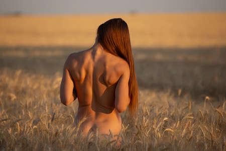 Achterkant van het lichaam vrouw op een veld, naakten in de natuur
