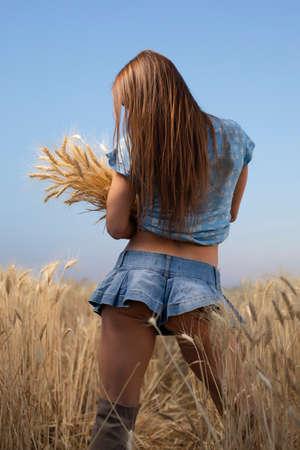 Femme paysanne sexy en mini jupe tenant des épillets de blé sur un champ