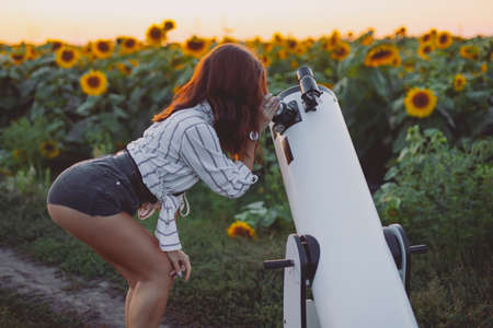 Mujer sexy mirando a través del telescopio en el cielo