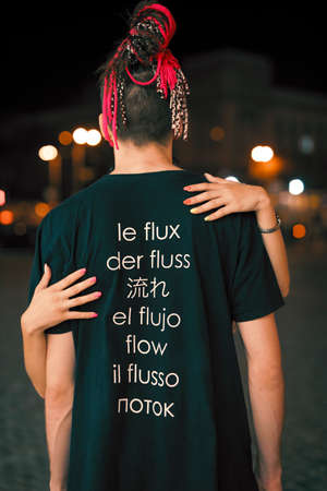 Man in t-shirt with word flow on different languages in night city, back view Stockfoto