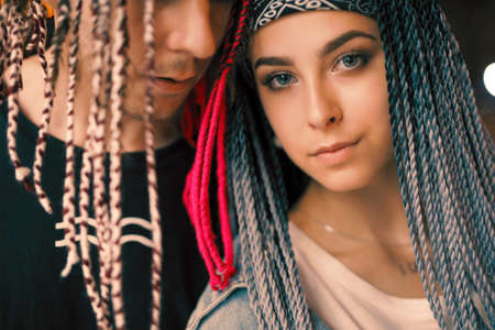 Unconventional young couple portrait at the night city with african colorful pigtails, trendy hairstyle