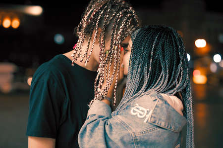 Unconventional young couple kisses at the night city Stockfoto