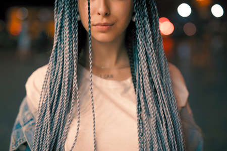 Cropped portrait of young unusual woman with blue pigtails in the night city