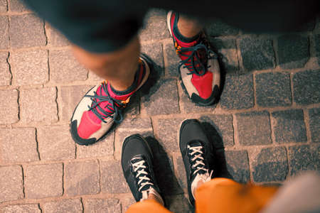 Couple legs in footwear standing together on pavement at night, pov view from above