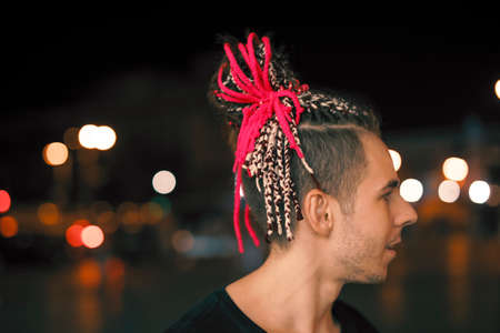 Profile view of young unusual man with red pigtails in night city