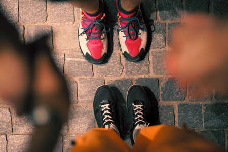 Couple legs in footwear standing together on pavement at night, view from above Stockfoto