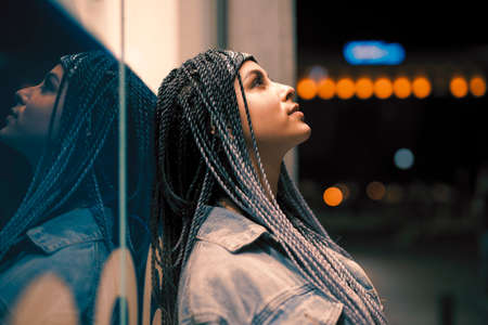 Portrait of young unusual woman leaning on building in the night city
