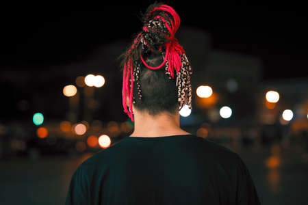 Back view of young unusual man with red pigtails in night city Stockfoto