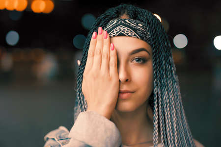 Portrait of young unusual woman with blue pigtails and hand close eye in night city Stockfoto