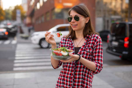 Young woman eating salad at urban city outdoor, fast dinner snack
