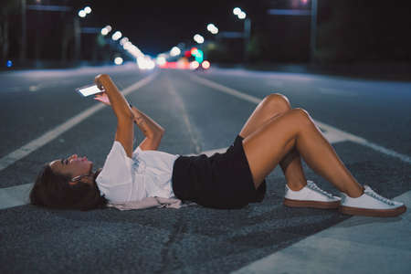 Woman in earbuds lying on night road listening music making selfie photo with her phone