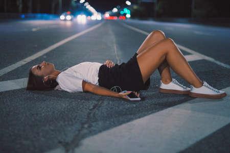 Portrait woman in earbuds lying on night road listening to music in earphones enjoying playlist songs on mobile