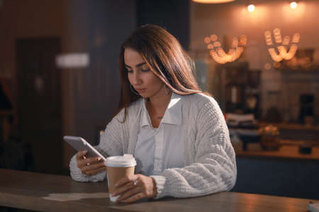 Attractive woman using mobile phone in cafe, view through window, send text message