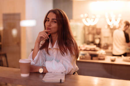 Attractive woman portrait sitting in cafe, view through window