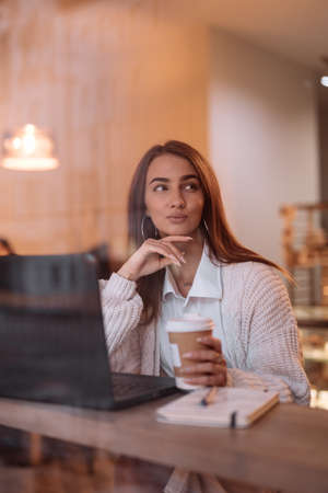 Woman working by laptop in cafe, view through window