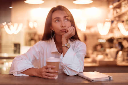Sad woman sitting in cafe leaning head on hand, view through window Stockfoto