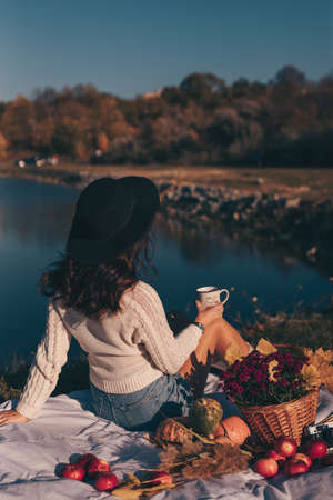 Art portrait of unrecognizable woman in hat on the nature sitting near lake drinking tea from cup Stock fotó