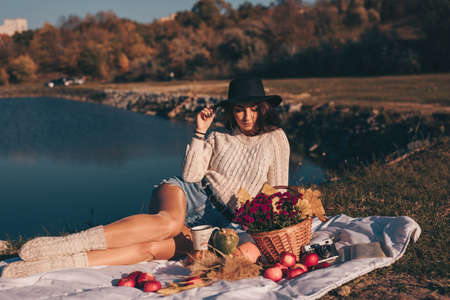Art portrait of woman in hat on the nature sitting near lake Stock Photo