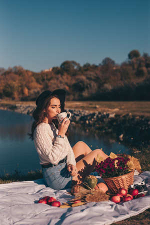 Art portrait of woman in hat on the nature sitting near lake drinking tea from cup Stock Photo