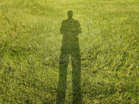 Shadow of man on green grass