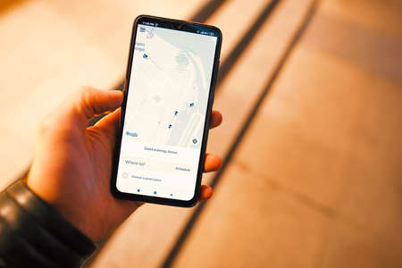 Dnipro  Ukraine, October 18, 2019: Male hand holding smartphone with Uber application at night city Editorial