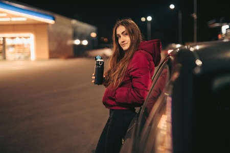 Portrait of woman driver holding thermo bottle leaning on car at gas station, night time