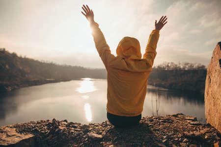 Traveler woman looking at sunset sitting near lake with raised hands enjoying freedom