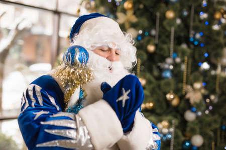 Blue Santa celebrating New Year holiday against Christmas tree Stock Photo