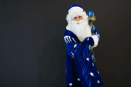 Happy blue Santa take a gift from his sack on black background Stock Photo