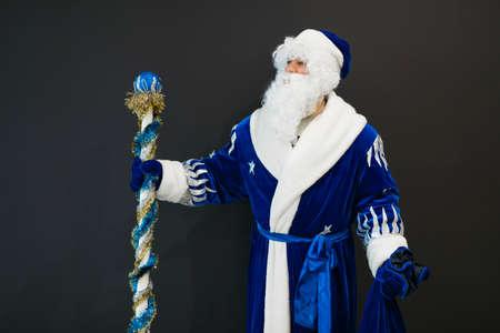 Portrait of blue Santa with stick on black background
