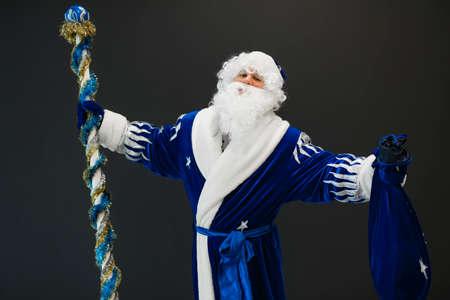 Happy blue Santa portrait celebrating Christmas holiday on black background with raised hands