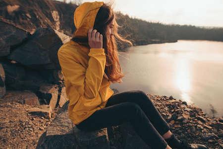 Hiker woman looking at sunset sitting near lake