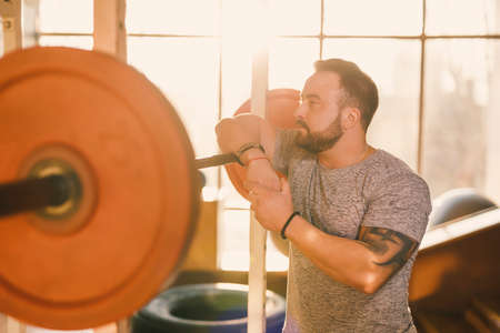 Portrait of confident strongman with barbell in the fitness gym