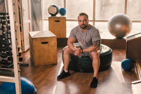 Portrait of athlete man with sitting on boxes in the fitness gym