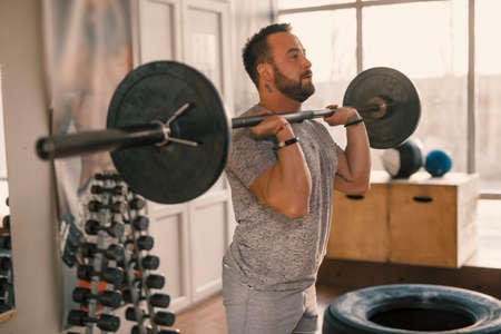 Man squat with barbell in a fitness gym making his muscles more strong