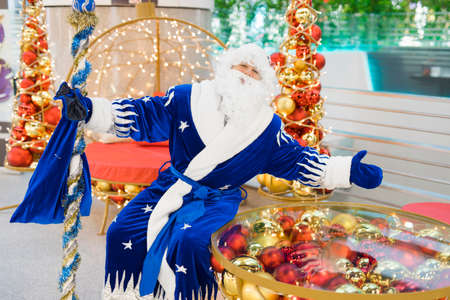 Portrait of blue Santa sitting on bench in Christmas decorations wants to hug Stock Photo