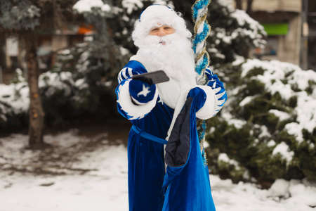 Blue Santa make a gift and give a smartphone to you