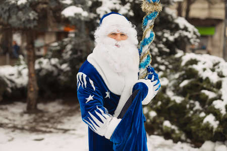 Blue Santa takes a gift from a bag sack in the winter city