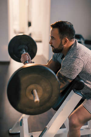 Man lifting barbell in a gym on EZ bar preacher curl, making biceps exercise
