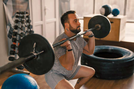 Man make front squat with barbell in a fitness gym making his legs muscles more strong Stock Photo