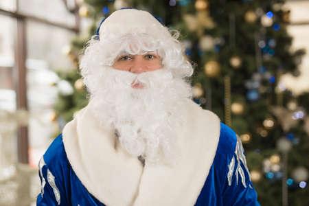 Blue Santa portrait near Christmas tree with copyspace